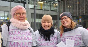 Kolme vapaaehtoistamme yhdistyksemme paidoissa Kampissa Helsingiussä